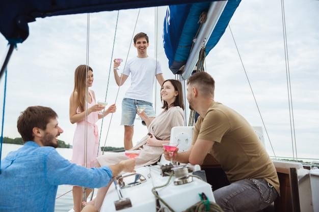 Группа счастливых друзей, пьющих водочные коктейли в лодке Бесплатные Фотографии