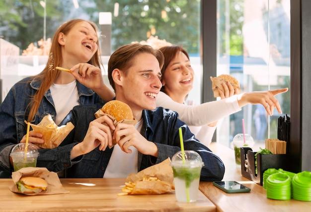 Группа счастливых друзей, едящих гамбургеры Бесплатные Фотографии