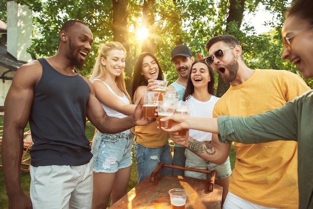 晴れた日にビールとバーベキューパーティーをしている幸せな友人のグループ。森の空き地や裏庭で屋外で一緒に休む 無料写真