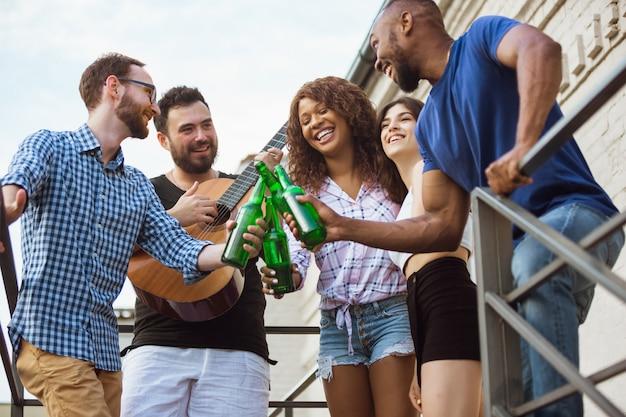 Группа в составе счастливые друзья имея вечеринку пива в летнем дне. отдыхаем вместе на свежем воздухе, празднуем и отдыхаем, смеемся. летний образ жизни, концепция дружбы. Бесплатные Фотографии