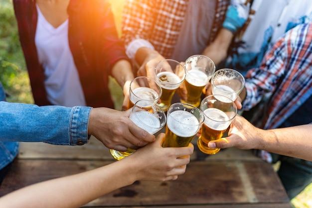 健康的なライフスタイルを生き、ビールとビールを飲みながら応援をリラックスして幸せな友人のグループ Premium写真