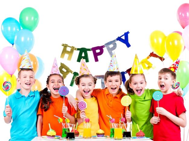 Группа счастливых детей с красочными конфетами, весело на вечеринке по случаю дня рождения - изолированные на белом. Бесплатные Фотографии