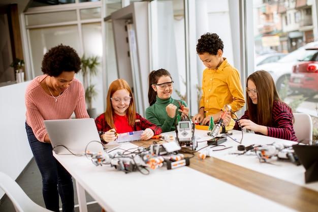 ロボット工学の教室でラップトッププログラミング電気おもちゃとロボットを持つアフリカ系アメリカ人の女性科学教師と幸せな子供たちのグループ Premium写真