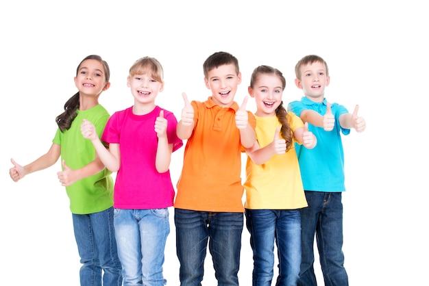 엄지 손가락으로 행복 한 아이 그룹 흰색 절연 함께 서있는 화려한 티셔츠에 가입. 무료 사진