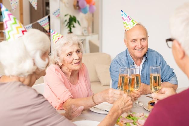 Группа счастливых старших друзей, чокающихся бокалом шампанского у обслуживаемого стола Premium Фотографии