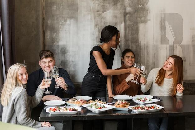 夕食を楽しんで幸せな若い人たちのグループ 無料写真