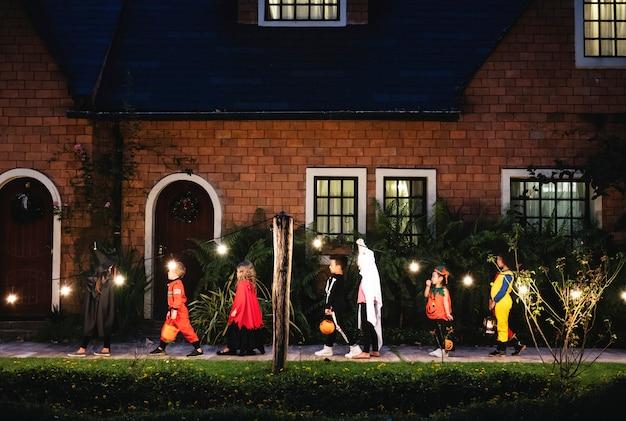 Группа детей с костюмами хэллоуина, идущими к трюку или лечению Бесплатные Фотографии