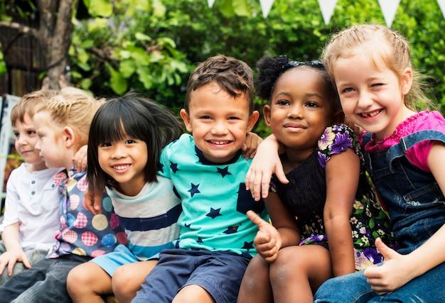 Группа детского сада дети друзья руки вокруг сидя и улыбается весело Premium Фотографии