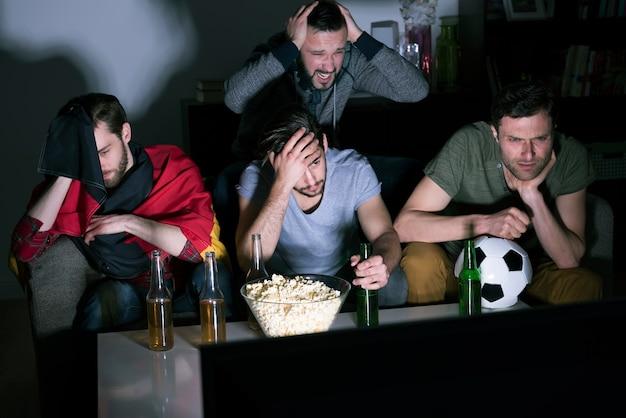 Группа мужчин пьет пиво и смотрит футбол по телевизору Бесплатные Фотографии
