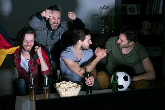 맥주를 마시고 Tv에서 축구를 보는 남자의 그룹 무료 사진