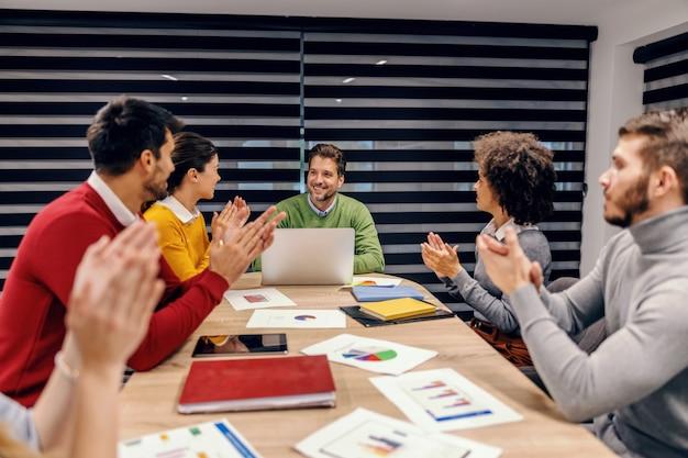 Группа мультикультурных коллег аплодирует своему коллеге. фирма выполнила ежемесячную денежную цель. Premium Фотографии