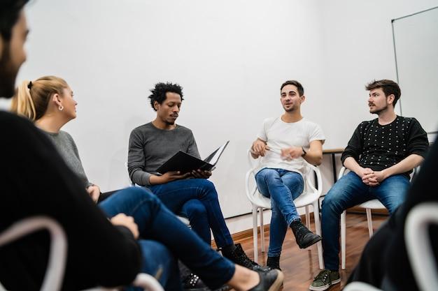 プロジェクトに取り組んでおり、ブレーンストーミング会議を行っている多民族の創造的なビジネスマンのグループ。チームワークとブレーンストーミングのコンセプト。 無料写真