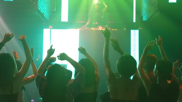 Группа людей танцует в ночном диско-клубе под музыку ди-джея на сцене Premium Фотографии