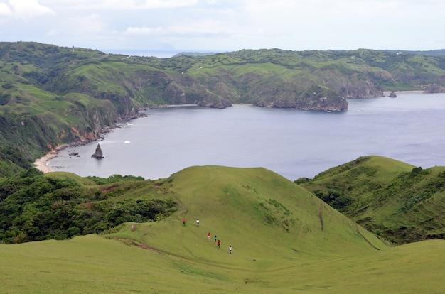 青空の下で緑に囲まれた海の周りの山をハイキングする人々のグループ 無料写真