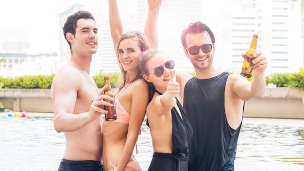 ビールのボトルとプールのそばで踊る夏服の人々のグループ Premium写真