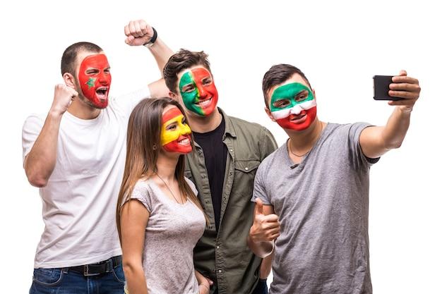 Группа сторонников болельщиков сборных разрисовала лица флагов португалии, испании, марокко, ирана и делает селфи с телефона. поклонники эмоций. Бесплатные Фотографии