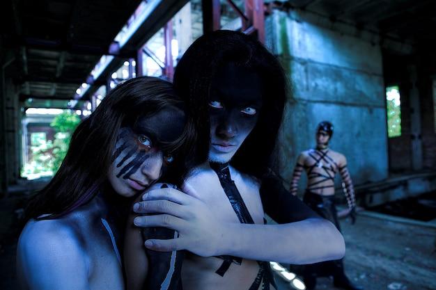 Группа людей с агрессивным фейс-артом. зомби-стиль. выстрел в разрушенное здание Premium Фотографии