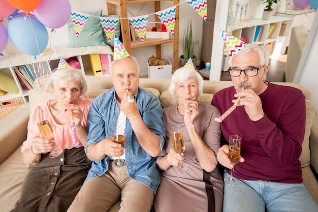 Группа старших друзей или две пары со свистком с шампанским на дне рождения Premium Фотографии