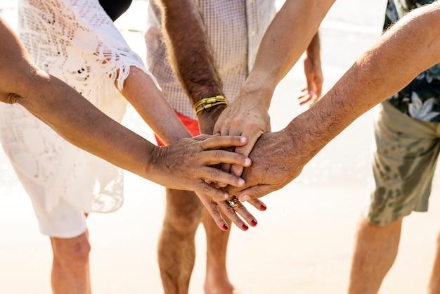 Группа старших друзей, складывающих руки Premium Фотографии
