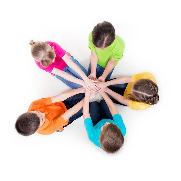 手をつないで円で床に座っている笑顔の子供たちのグループ-白で隔離。 無料写真