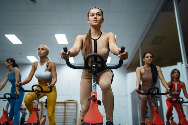 ジム、フロントでエアロバイクで運動をしているスポーツ女性のグループ Premium写真