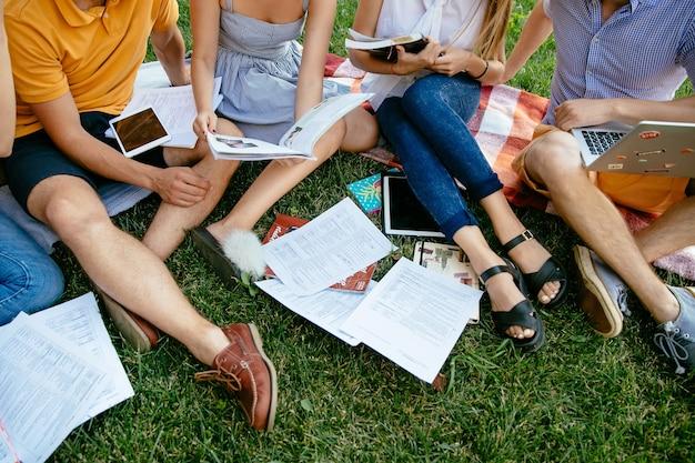 本とタブレットを持つ学生のグループは、一緒に屋外で草の根に座って勉強しています。 無料写真