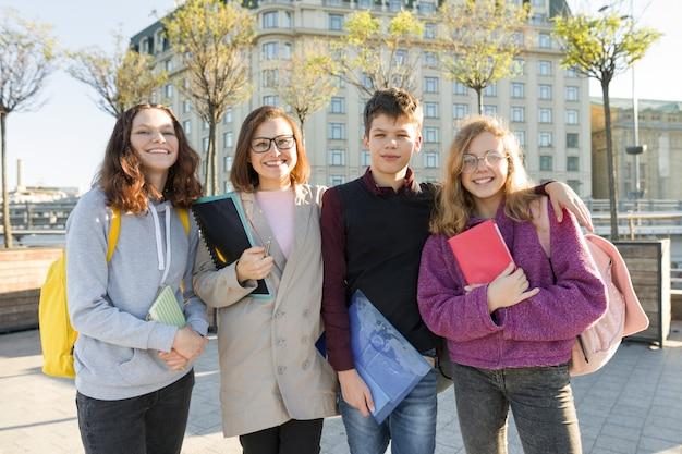 Группа студентов с учителем, подростки разговаривают с учительницей Premium Фотографии