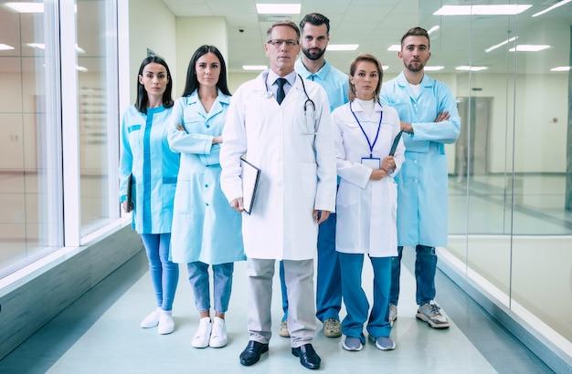 Группа успешных и уверенных в себе современных врачей позируют и смотрят в камеру в коридоре больницы Premium Фотографии