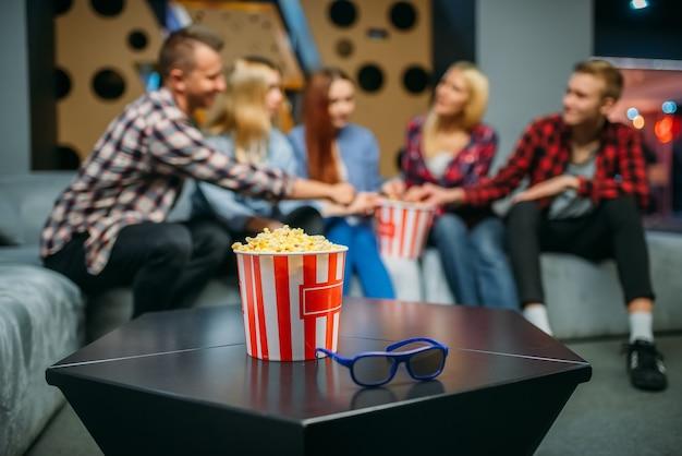 Группа подростков отдыхает на диване в кинозале Premium Фотографии