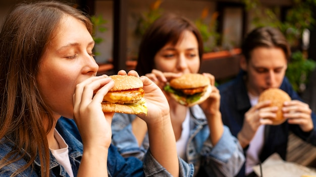 Группа трех друзей, наслаждающихся гамбургерами Бесплатные Фотографии