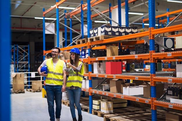Группа складских рабочих в касках и светоотражающих куртках просыпается в проходе между высокими стеллажами с пакетами и товарами Бесплатные Фотографии
