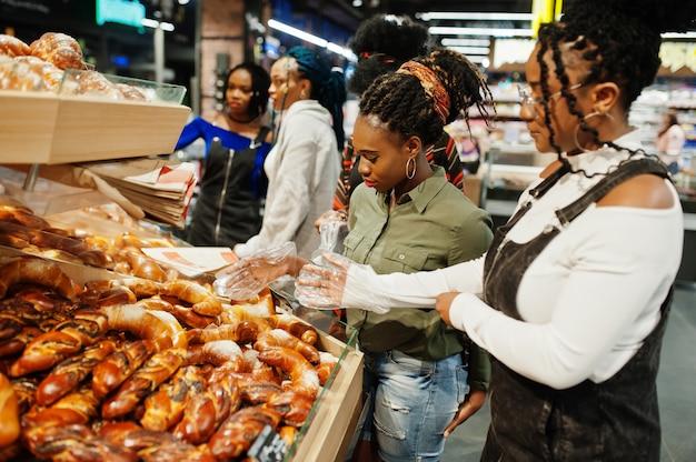 スーパーマーケットで焼き製品の近くのショッピングカートを持つ女性のグループ Premium写真