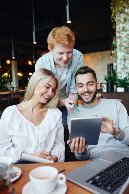 カフェでの会議で情報をスクロールしながらタッチパッドのディスプレイで面白いものを笑っている若い大学生のグループ Premium写真