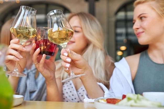 カフェで飲み物とグラスをチリンと鳴らす若い友人のグループ Premium写真