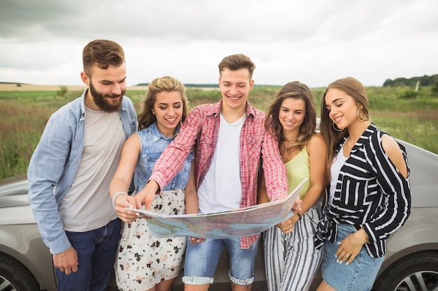 Group of young friends standing by the car looking at map Free Photo