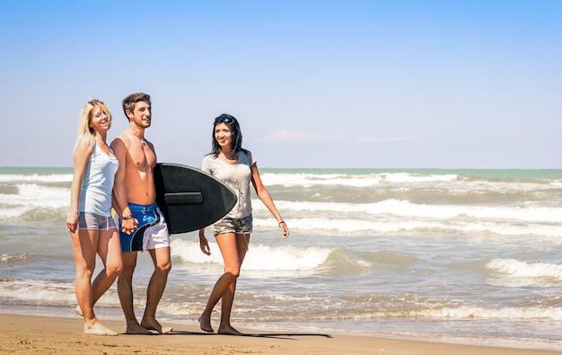 Группа молодых счастливых людей на каникулах на пляже, держа доску для серфинга Premium Фотографии