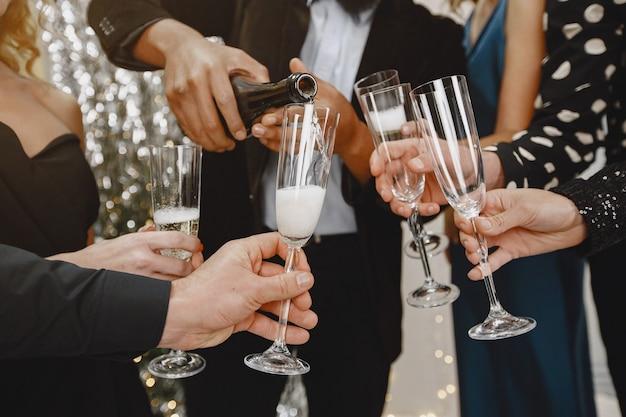 Группа молодых людей, празднующих новый год. друзья пьют шампанское. Бесплатные Фотографии