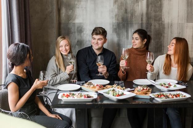 夕食とワインを一緒に楽しんでいる若者のグループ 無料写真