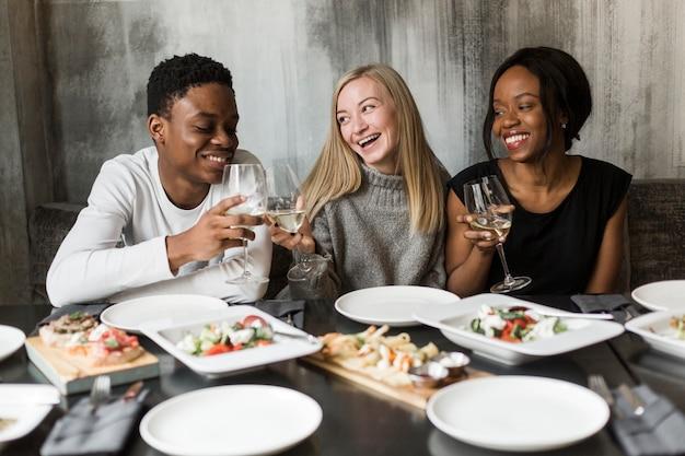 夕食とワインを楽しむ若者のグループ 無料写真