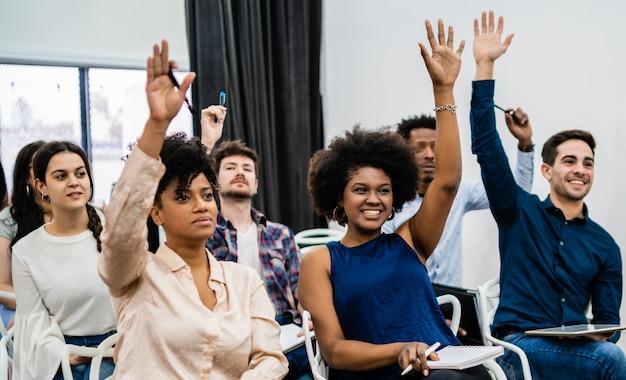 Группа молодых людей, сидящих на конференции вместе Бесплатные Фотографии