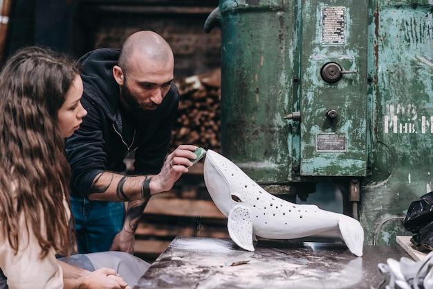 Group of people enjoying favorite job in workshop. people carefully work on ceramic whales Free Photo