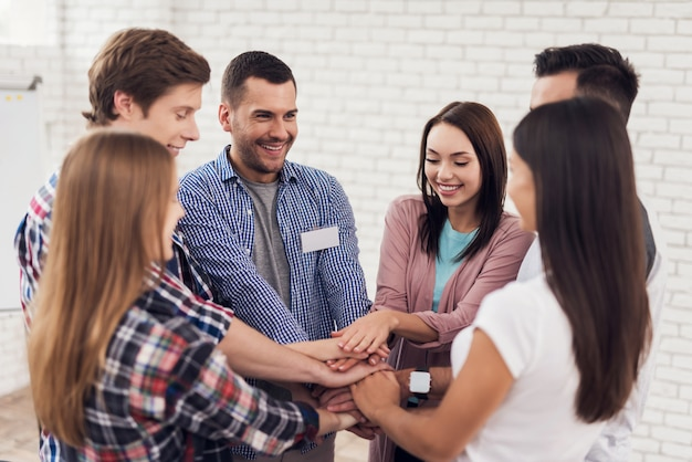Group of people gathered in circle and held hands. Premium Photo