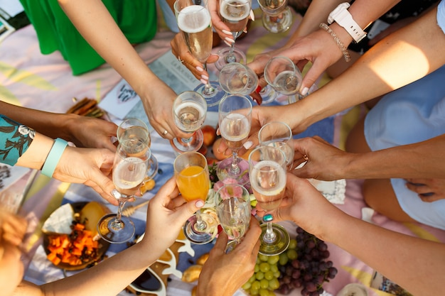 Group of people having outdoor picnic meal togetherness dining toasting glasses. summer weekends Premium Photo