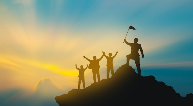 Group of people on mountains top in winner pose. teamwork concept Premium Photo