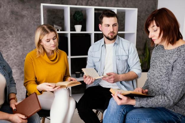 Gruppo di persone che leggono libri alla sessione di terapia Foto Gratuite