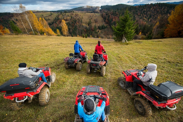 Group of people riding a quad bikes on hill Premium Photo