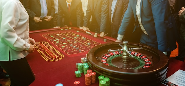 Group of people behind roulette gambling table in luxury casino Premium Photo