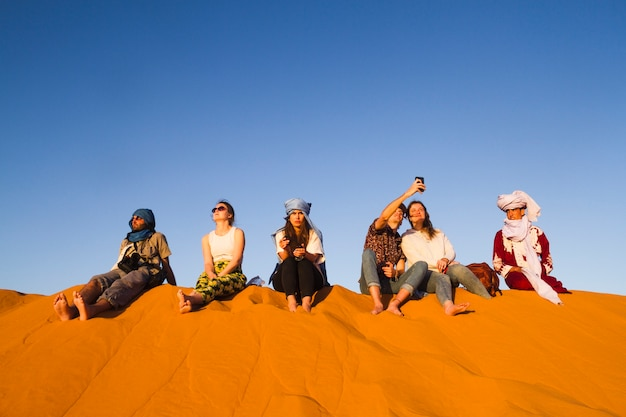 Group of people sitting on top of dune Free Photo