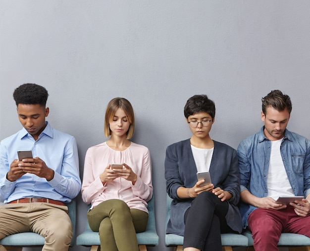 Gruppo di persone sedute in sala d'attesa Foto Gratuite