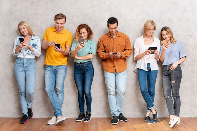 Group of people standing and checking devices Free Photo